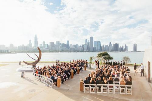 A shot of a wedding taking place right outside of the Adler, with the Chicago skyline in view in the background.